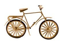 Kleine gouden kleurenstuk speelgoed fiets die op wit wordt geïsoleerdg royalty-vrije stock foto's