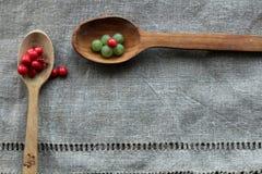 Kleine grüne Beeren von Trauben und rote Beeren des Lemongrases auf zwei hölzernen Löffeln, die auf einem Stoff gemacht vom Sackl stockfoto
