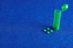 Kleine grüne Pillen mit einem kleinen grünen Tablettenfläschchen Lizenzfreies Stockbild
