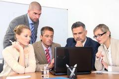 Kleine groep bedrijfsmensen die aan laptop werken Stock Foto's