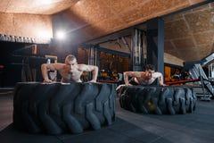 Kleine groep die mensen opdrukoefeningen op band doen Jonge atleten die op strand tijdens een hete de zomerdag uitwerken Stock Afbeelding