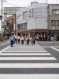 Kleine Gruppe von Personen, welche die Straße kreuzt Stockbilder