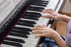 Kleine Hände auf Klavier Stockbild