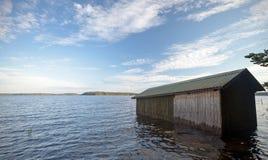 Kleine hölzerne Bootsgarage auf der Küste Stockfotografie