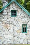 Kleine hölzerne Fenster und Kaminstapel in einem Steinhäuschen mit grüner Ordnung und Giebel lizenzfreie stockfotos