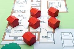 Kleine hölzerne Häuser auf einem Plan Stockfotografie