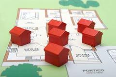 Kleine hölzerne Häuser auf einem Plan Stockbilder