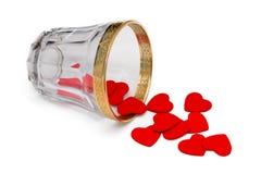 Kleine hölzerne Herzen, die aus Glas heraus verschüttet werden Stockfotos
