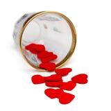 Kleine hölzerne Herzen, die aus Glas heraus verschüttet werden Lizenzfreie Stockfotografie