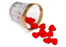 Kleine hölzerne Herzen, die aus Glas heraus verschüttet werden Lizenzfreie Stockbilder