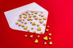 Kleine h?lzerne Herzen fliegen aus einem wei?en Umschlag auf einem roten Hintergrund heraus Valentinsgru? `s Tag Zu k?ssen Mann u lizenzfreie stockfotos