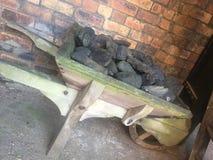 Kleine hölzerne Schubkarre gefüllt mit Kohle lizenzfreies stockbild