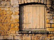 Kleine hölzerne Tür in einer Steinwand Lizenzfreie Stockbilder