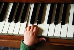 Kleine hand op piano Stock Afbeeldingen
