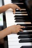 Kleine handen die op de piano spelen Stock Foto