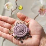 Kleine handgemachte Brosche in Form einer großen Blume vom Stoff auf der Palme einer Frauennahaufnahme Stockfoto