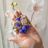 Kleine handgemachte Brosche in Form von zwei beige Blumen liegt auf der Palme einer Frau Lizenzfreies Stockbild