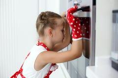 Kleine Hausfrau engagierte sich in den Backenmuffins in der Küche zu Hause Lizenzfreie Stockfotos