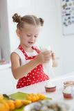 Kleine Hausfrau engagierte sich in den Backenmuffins in der Küche zu Hause Lizenzfreie Stockfotografie