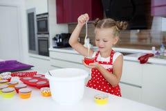 Kleine Hausfrau engagierte sich in den Backenmuffins in der Küche zu Hause Lizenzfreie Stockbilder