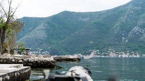 Kleine haven met groene bergen en water met mos in de kabels Schip in kotorbaai en kuststad Rotspijler voor kleine boten binnen stock foto's