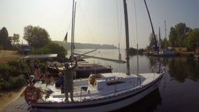 Kleine haven op zonnige dag, positieve zeelieden op sloependek stock video
