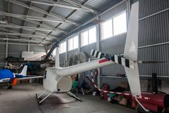 Kleine helikopter en een sportenvliegtuig in de hangaar Royalty-vrije Stock Fotografie