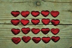 Kleine Herzen auf einem hölzernen Hintergrund Lizenzfreie Stockfotos