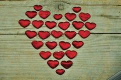Kleine Herzen auf einem hölzernen Hintergrund Stockfotografie
