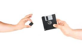 Kleine het Geheugenkaart van de handenholding tegenover Oude Diskette Royalty-vrije Stock Afbeelding