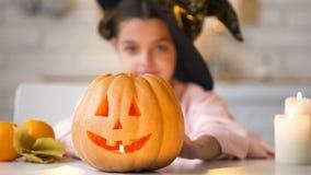 Kleine Hexe, die den furchtsamen Jack-O-Laternenkürbis, bereitend für Halloween-Partei zeigt vor lizenzfreie stockfotografie