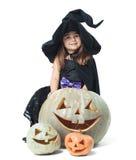 Kleine Hexe, die hinter Kürbisen sich versteckt Stockbild
