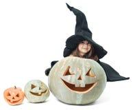 Kleine Hexe, die hinter Kürbisen sich versteckt Stockfotografie