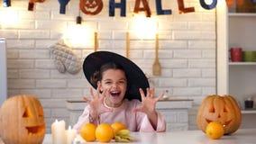 Kleine Hexe, die Leute, Kamera betrachtend erschrickt und haben Spaß an Halloween-Partei lizenzfreie stockbilder