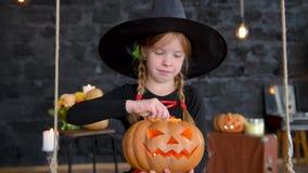 Kleine Hexen Childs auf Halloween auf einem schwarzen Hintergrund, Mädchen, das Kürbis mit einer brennenden Kerze hält stock footage
