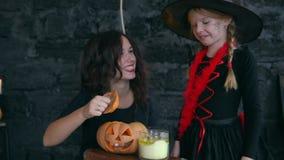 Kleine Hexen Childs auf Halloween auf einem schwarzen Hintergrund, Mädchen, das Kürbis mit einer brennenden Kerze hält stock video footage