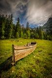Kleine houten boot door het meer Gosausee onder Dachstain op de groene weide van alpen dichtbij Kreidenbach stock afbeelding