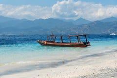 Kleine houten boot op blauw strand met bewolkte hemel en Lombok-eiland op achtergrond Gili Trawangan, Indonesië Stock Afbeelding