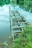 Kleine houten brug in meer met bezinning van bomen Stock Foto