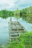 Kleine houten brug in meer met bezinning van bomen Stock Afbeelding