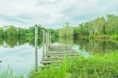 Kleine houten brug in meer met bezinning van bomen Royalty-vrije Stock Afbeeldingen