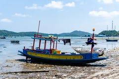 Kleine houten vissersboten die bij het vuile strand vastleggen Stock Foto