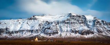 Kleine Ijslandse kerk onder sneeuw afgedekte bergen Stock Afbeelding