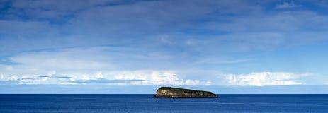 Kleine Insel im blauen Meer Stockfotos