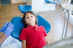 Kleine jong geitje geduldige bezoekende specialist in tandkliniek stock foto