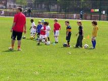 Kleine jonge geitjes bij voetbal de opleiding in het park stock fotografie