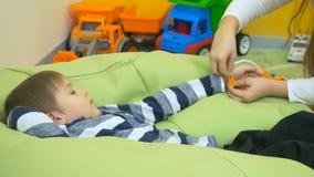 Kleine jonge geitjes die arts met stuk speelgoed tonometer in kinderen` s ruimte spelen stock videobeelden