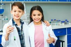 Kleine jonge geitjes die chemie in de installatie van het schoollaboratorium in een test-buis leren stock fotografie