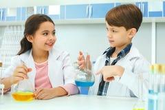 Kleine jonge geitjes die chemie in het experimentingrediënten van het schoollaboratorium leren royalty-vrije stock foto