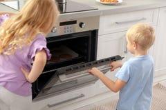 Kleine jonge geitjes die koekjes in oven bakken royalty-vrije stock afbeelding